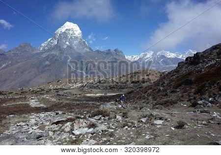 Trekker hiking on the trail to Ama Dablam base camp with Tabuche peak on backdrop - acclimatization day trip from Pangboche village, Everest trek, Sagarmatha national park, Solukhumbu, Nepal