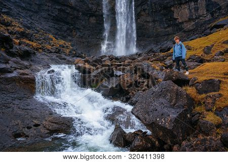 Tourist Standing At The Fossa Waterfall On Island Bordoy In The Faroe Islands, Denmark