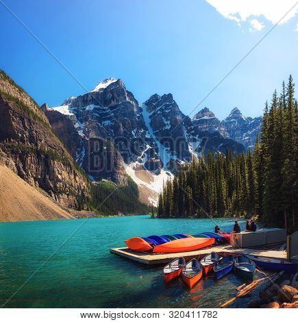 Canoes On A Jetty At Moraine Lake In Banff National Park, Alberta, Canada, With Snow-covered Peaks O