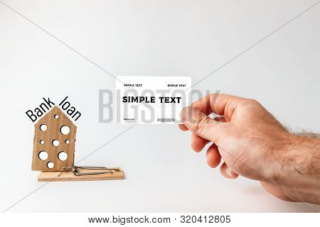 Concept of Bank investments and risks. A mans hand holds a Bank card, and next to it is a mousetrap with a cardboard house with a cheese texture. Text BANK and LOAN. Mock up and copy space poster