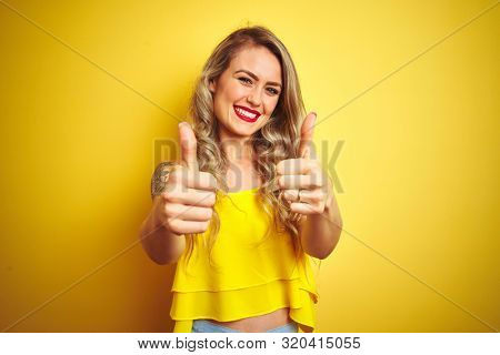 Young attactive woman wearing t-shirt standing over yellow isolated background approving doing positive gesture with hand, thumbs up smiling and happy for success. Winner gesture.