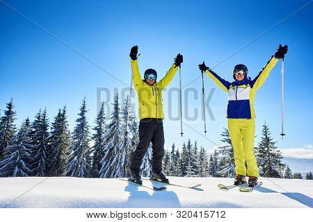 Smiling Couple Of Skiers In Goggles With Reflection, Posing On Skis With Ski Poles In Hands Up On Sn