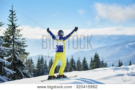 Back View Of Female On Skis Rejoicing On Snow-covered Edge Of Mountain Top. Skier Raising Hands Up W