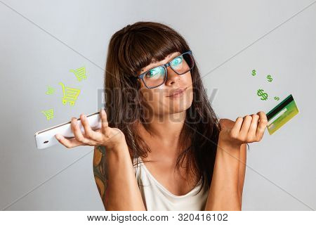 Finance And Bank Cards. A Woman With Glasses And Tattoos Holds A Bank Card And A Mobile Phone In Her