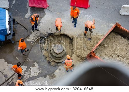 Many Workers In Orange Vests Repair Storm Sewer Or Rain Collector Or Cesspit On Road With Help Of Te