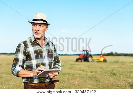 Cheerful Self-employed Farmer In Straw Hat Using Digital Tablet In Field