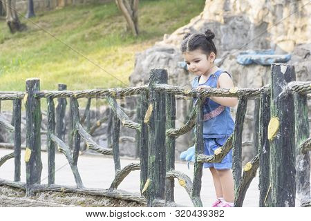 Little Girl Stayed Behind Enclosed Hedge And Looking Around At Park, Childhood Memories Concept
