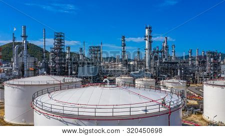 Oil​ Refinery​ And​ Petrochemical​ Plant Industrial Working With Fire And Blue Sky Background, Aeria