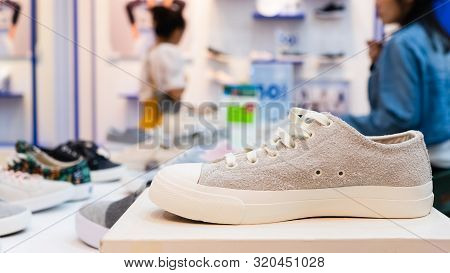 White Sneakers On The Display Table In The Fashion Shoes Store, Close-up With Blurred Background Of