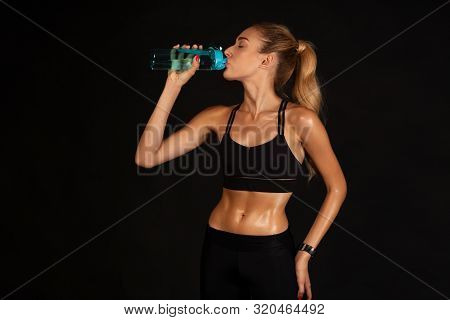 Fit Woman Drinking Water After Exercising Over Black Studio Background. Workout Break Concept. Free