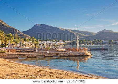 Stone pier with tables and umbrellas cafe in early morning in Port de Pollenca, Mallorca, Balearic islands, Spain