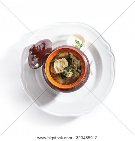 Traditional Russian dumplings in a clay ceramic pot with finely chopped dill and sour cream isolated. Top view of dumplings, jiaozi, dimsum or momo stuffed with meat, fish and vegetables topview