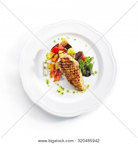Top Viewt of grilled chicken fillet with side dish of baked vegetables on white restaurant plate isolated. Bbq chicken breasts or white meat barbecue with fried zucchini and bell pepper topview