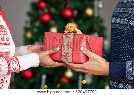 Young couple wearing christmas theme sweater exchanging gifts in front of decorated christmas tree. Closeup of african woman hand receive xmas present from her boyfriend.