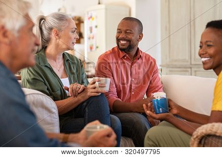 Senior and mature couples in conversation at home. Cheerful multiethnic group of people enjoying a cup of tea while talking to each other. Group of senior people socializing over coffee.