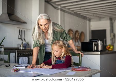 Old grandmother helping granddaughter while studying at home. Senior teacher helping little girl student with homework. Elementary student doing homework at grandma's house after school.