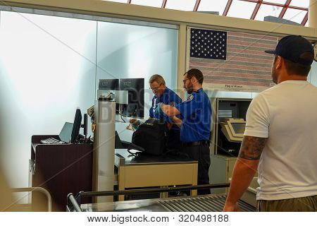 Bloomington,il/usa-8/25/19: Two Tsa Security Employees Checking A Backpack For  Potentially Dangerou