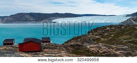 Greenland glacier nature landscape with famous Eqi glacier and lodge cabins. Tourist destination Eqi glacier in West Greenland AKA Ilulissat and Jakobshavn Glacier. Heavlly affected by Global Warming.