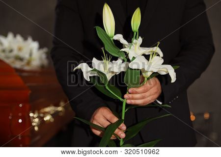 Young Man With White Lilies In Funeral Home, Closeup