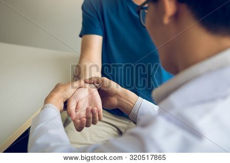 Physical Therapist Checks The Patient Wrist By Pressing The Wrist Bone In Clinic Room.
