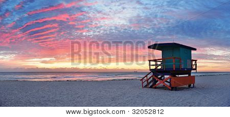 Miami South Beach sunrise with lifeguard tower and coastline with colorful cloud and blue sky. poster