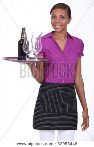 Pretty waitress carrying a bottle of beer and two glasses on a tray