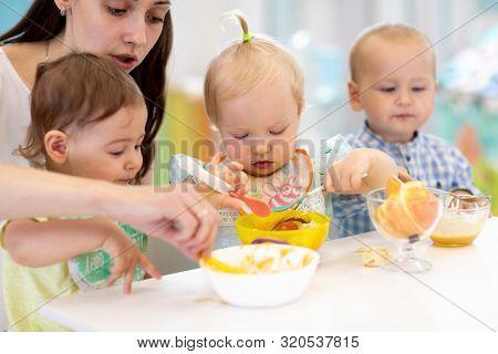 Group Of Nursery Babies Eating Healthy Food With Kindergartener Help. Lunch Break In Creche. Little