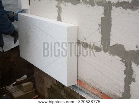 Insulation House Wall Outdoors. Builder Installing Rigid Styrofoam Insulation Board For Energy Savin