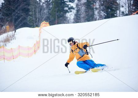 Front View Of Young Skier Concentrated On Skiing Down On Steep Ski Slope. Proficient Technical Carvi