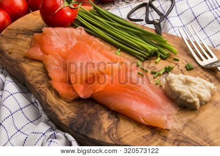 Scottish Smoked Salmon On A Wooden Board With Chive, Tomato, Horseradish And Fork