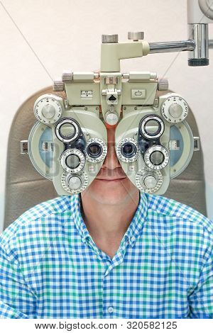 A Man Checks Eyesight In A Clinician Oculist. Man Checks His Vision On The Machine Checking Patient