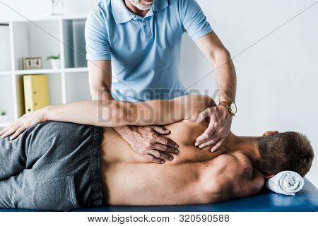 Cropped View Of Chiropractor Touching Back Of Man On Massage Table