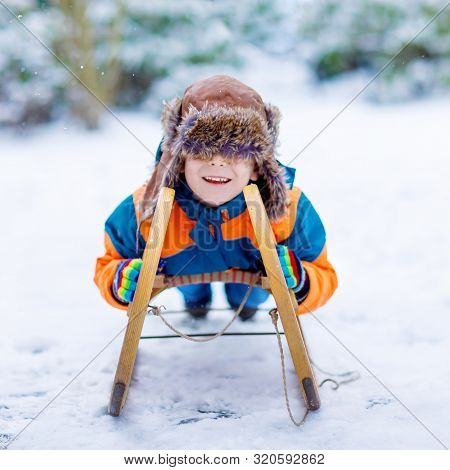 Little School Boy Having Fun With Sleigh Ride During Snowfall. Hapy Child Sledding On Snow. Preschoo