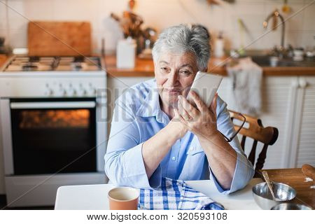 Senior Woman Is Using Mobile Phone In Cozy Kitchen At Home. Retired Person Has Coffee Break With Dev