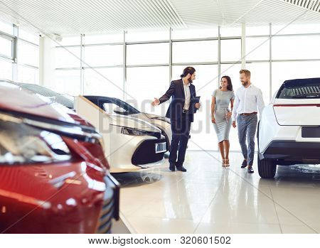 Couple And The Dealer Selling Cars Look The Car In The Showroom.