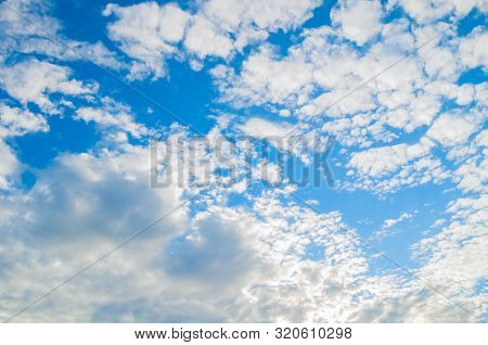 Dramatic blue sky background - picturesque colorful clouds lit by sunlight. Vast sky landscape panoramic scene. Colorful sky view in bright tones