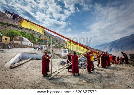 DHANKAR, INDIA - JULY 2, 2012: Tibetan Buddhist monks of Dhankar gompa setting up the pole with prayer flags. Dhankar, Spiti valley, Himachal Pradesh, India