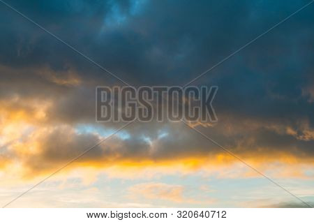 Blue dramatic sunset sky background - picturesque colorful sky clouds lit by sunlight. Vast sky landscape panoramic scene, sunset sky evening view