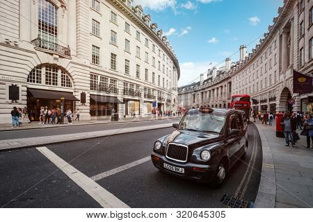 LONDON,UK - AUGUST 19,2019 : Typical London taxi and double decker bus at the famous Regent Street in central London