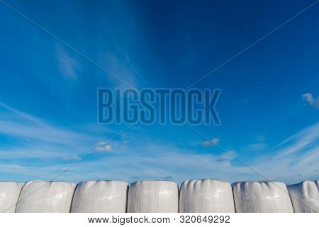 A Row Of Silages In Front Of Blue Sky
