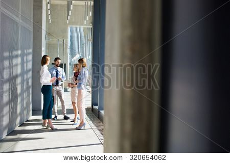 Business people discussing plans while standing in office corridor