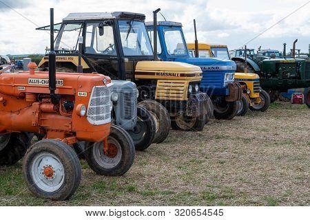 Haselbury Plucknett.somerset.united Kingdom.august 18th 2019.a Row Of Vintage Tractors Are On Displa