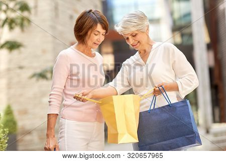 sale, consumerism and people concept - two senior women or friends with shopping bags on tallinn city street