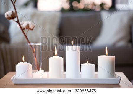 decoration, hygge and cosiness concept - burning white candles and cotton flower branch on table at cozy home