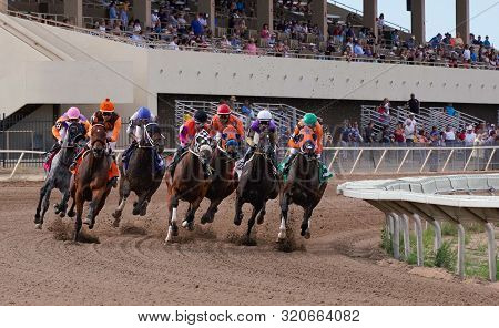 Horses And Jockeys Round The First Bend On The Racetrack At Arizona Downs In Prescott, Arizona On Se