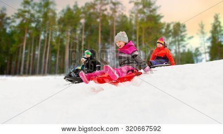 childhood, sledging and season concept - group of happy little kids sliding on sleds down snow hill in winter over forest background