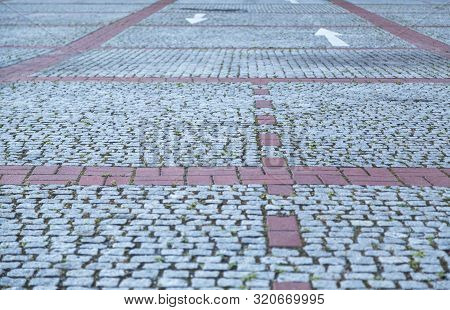 Cobble Stone Street With Red Lines And White Arrows