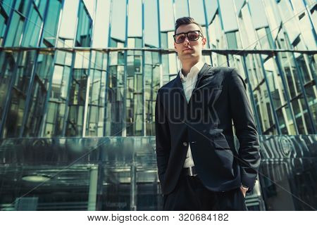 A portrait of a goodlooking young guy walking in the street. Men's beauty, fashion, business.