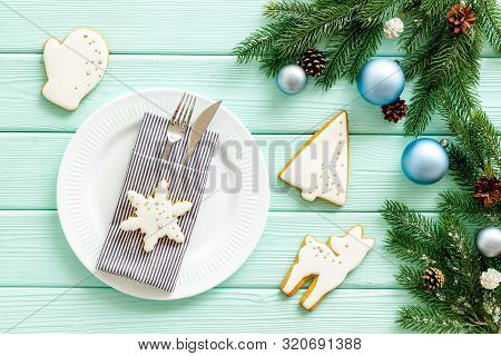 Table Setting With Spruce, Plate, Flatware On Mint Green Wooden Background Top View