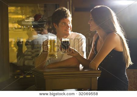 Young couple on a date enjoying their drink in a pub/bar